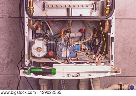 The Master Installs A Gas Boiler That Hangs On The Wall. The Front Dashboard Is Open. The Heating Is
