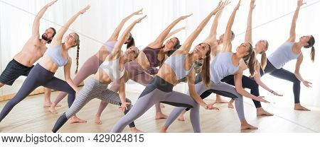 Group Of Young Sporty Attractive People In Yoga Studio, Practicing Yoga Lesson With Instructor, Stre