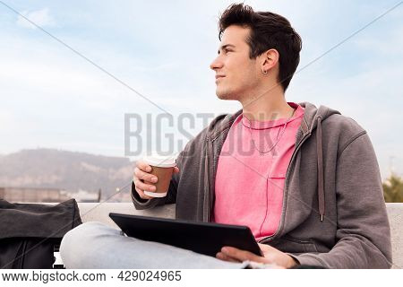 Young Man Sitting Outdoors With Coffee Using A Tablet, Concept Of Technology And Urban Lifestyle, Co