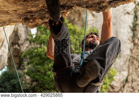 Climber Man Avoiding A Difficult Obstacle In His Ascent To The Mountain. Extreme Sports And Mountain