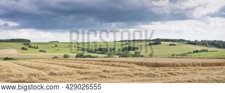 Cloudy Sky Over Summer Countryside Landscape With Green Meadows And Corn Fields In French Ardennes N