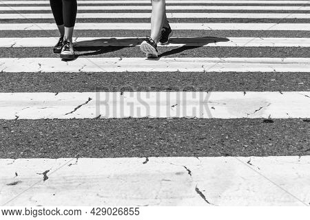 Pedestrian Crossing City Downtown Girls Walk In Motion On Road. Legs, Feet And Shoes From Two Young