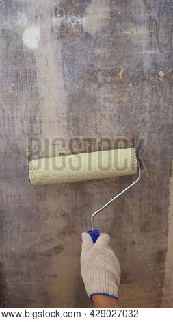Painters Hand Holds Paint Roller, Painting Wall With White Color. Close-up Of Hand Painting Wall. Ha