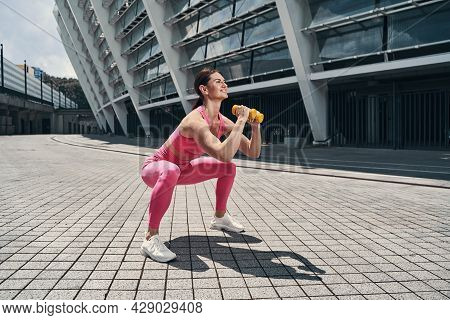 Adult Doing Squat Exercise On Empty Street