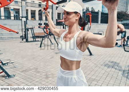 Female Taking Handles Of Cable Lat Pull-down