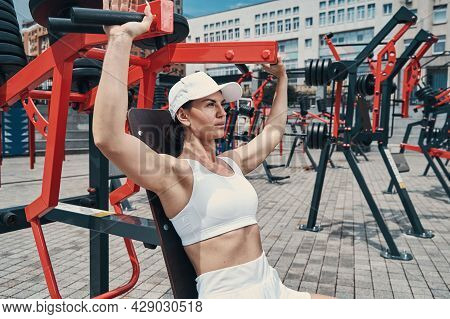 Female Sitting On Exercise Machine And Pulling Down Its Handles