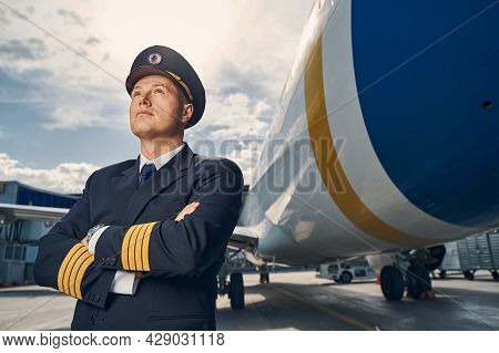 Pilot Dressed In Uniform Gazing Up At The Sky