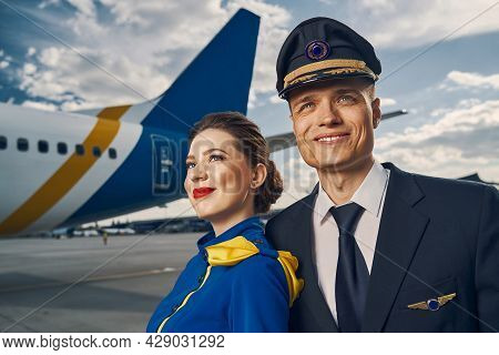 Smiling Pilot And A Flight Attendant Standing At The Aerodrome