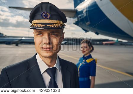 Airline Pilot And A Dark-haired Stewardess Standing At The Airdrome
