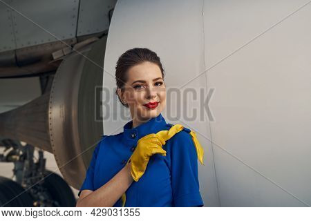Serene Flight Attendant Standing By A Landed Airliner
