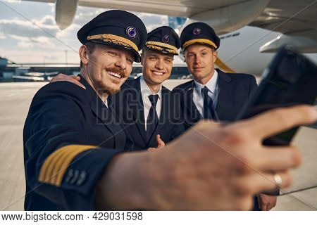 Three Airmen In Uniforms Taking Selfies At The Airport