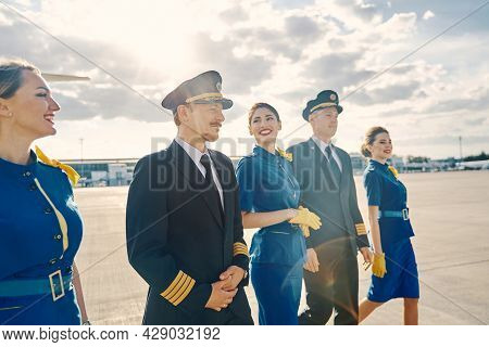 Happy Female Flight Attendants And Airline Pilots Going Ahead