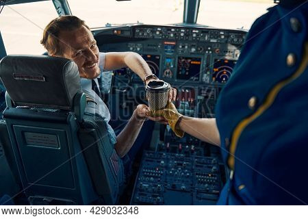 Airline Captain Being Served Coffee In The Cockpit