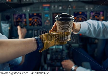 Pilot Hand Reaching For A Disposable Paper Cup Of Coffee