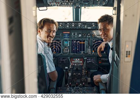 Joyous Pilot And A Co-pilot Looking Out Of The Cockpit