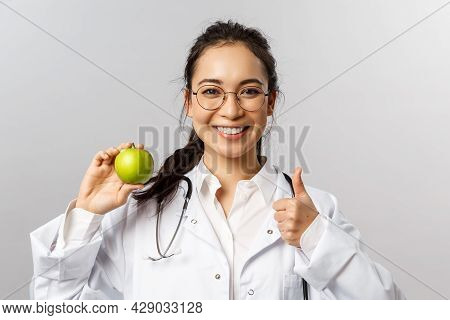 Portrait Of Young Cheerful Asian Female Doctor, Therapist Or Diatologist Talking Abut Healthy Diet,