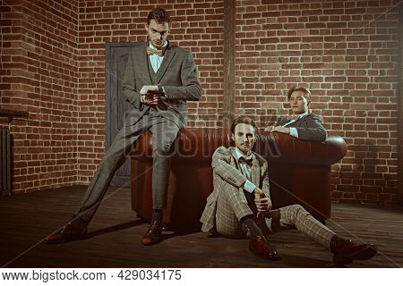 Business people club. Three handsome men in elegant are posing in apartments with loft interior. Men's fashion.