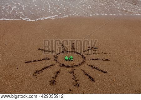 Symbol Of The Sun And A Family By The Sea. Painted Sun On The Sand, Sea Coast, Figure Of A Green Fam