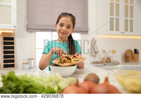 Little Girl With Cutting Board And Knife Scraping  Vegetable Peels Into Bowl In Kitchen
