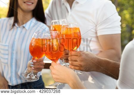 Friends Clinking Glasses Of Aperol Spritz Cocktails Outdoors, Closeup