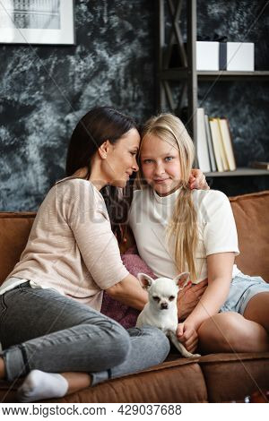 Mother and daughter relationship concept. A woman and a teenage girl are sitting in front of the TV on the couch and have fun talking. The family spends time at home. Little dog lying on laps