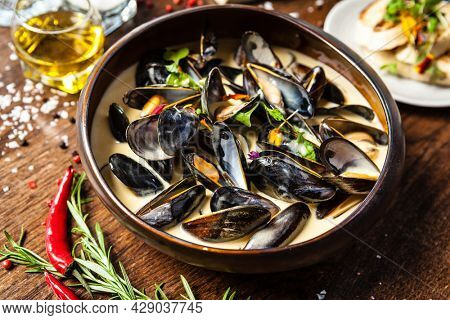 Blue mussels in cream wine sauce. Delicious healthy Italian traditional food closeup served for lunch in modern gourmet cuisine restaurant