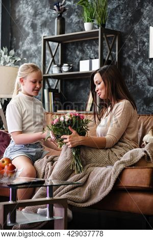 Mother and daughter relationship concept. A teenage girl congratulates happy woman on her birthday and gives her flowers and gift. The family celebrates anniversary or mother's day at home