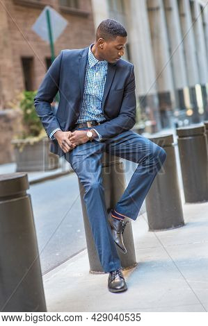 Lowing His Head, A Young Black Businessman Is Sitting Outside And Into Deeply Thinking