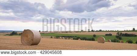 Landscape With Straw Bales In French Ardennes Under Cloudy Sky During Sunset In Summer