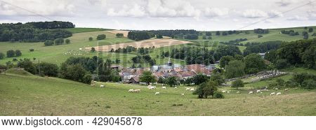Cloudy Sky Over Summer Countryside Landscape With Green Meadows And Village With Cattle In French Ar