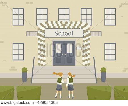 Two Classmates, Classfellows Or Friends Walk And Talk Or Chat Near Brick School Building.entrance To