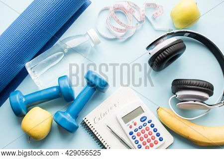 Paper Notebook, Calculator, Pen, Dunbbell And Fruits On Blue Background. Weight Loss, Fitness, Count