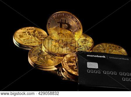 Lutsk, Ukraine - May 1, 2021: Golden Coin With Bitcoin Logo And Credit Card By Monobank. Crypto Curr
