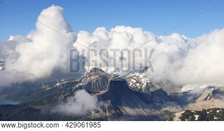 Aerial View From Airplane Of Canadian Mountain Landscape. Sunny Summer Clouds. Garibaldi Between Squ