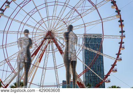 Batumi, Georgia - July 2, 2021: Ali And Nino Statue And The Ferris Wheel In Batumi, Adjara, Georgia.