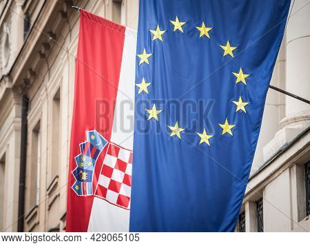 Croatian And European Flags Waiving In The Air With A Building In Background. Croatia Is The Younges
