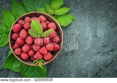 Appetizing Juicy Ripe Raspberries In A Bowl Surrounded By Green Raspberry Leaves On A Black Backgrou
