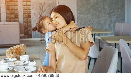 Toddler Daughter Hugs Mom. Little Child Girl Hugs Asian Mum Brunette With Smile Near Table With Whit