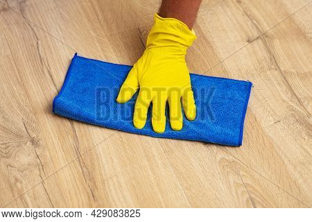 Gloved Hand Washing A Laminate Flooring With A Wet Cloth