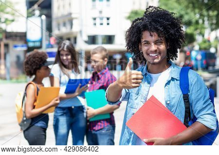 Optimistic Mexican Male Student With Other Young Adults Outdoor In Summer In City