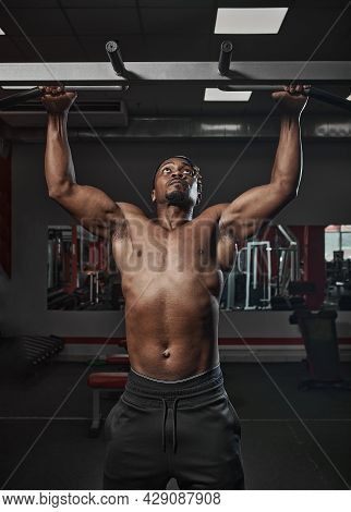 Athletic African American Man With Naked Torso Doing Chin-ups Or Pull Ups Exercising On Training In