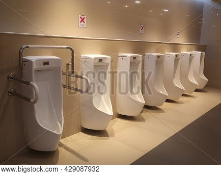 Contemporary Interior Of Public Toilet. Clean White Urinals In A Public Restroom. Public Gentlemen T