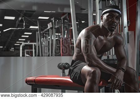 Athletic African American Tired Guy Have A Break Sitting On Sports Bench During Training In Gym. Spo