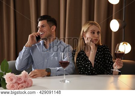 Man Talking On Phone Instead Of Spending Time With Young Woman During First Date In Restaurant