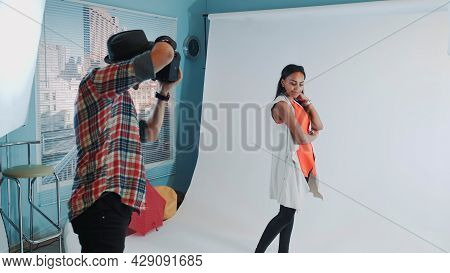 Behind The Scenes On Photo Shoot: Professional Photographer Working In Studio By Taking Photos Of Bl