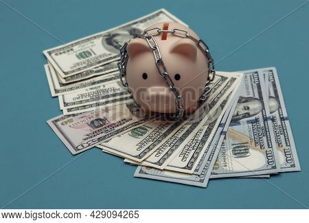Piggy Bank Wrapped In Steel Chain And Hundred Dollar Bills On Blue Background