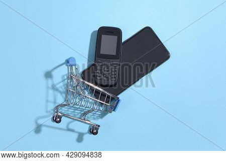 Shopping Trolley With Push-button Telephone And Modern Smartphone On Blue Background. Top View