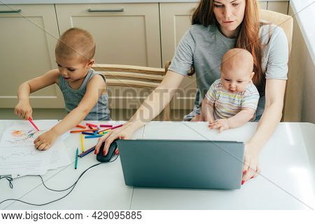 A Working Business Woman With A Baby In Her Arms Works On A Laptop, Next To A Toddler Draws. Busy Co