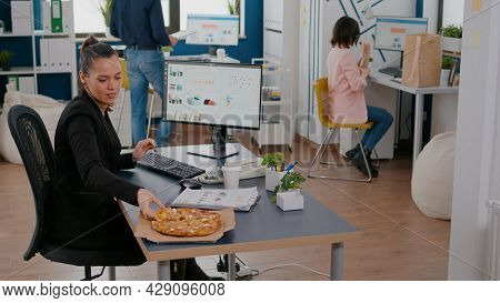 Businesswoman On Lunch Break At Her Table Eating Pizza Fastfood Delivery. Takeaway Delivery Meal Ord