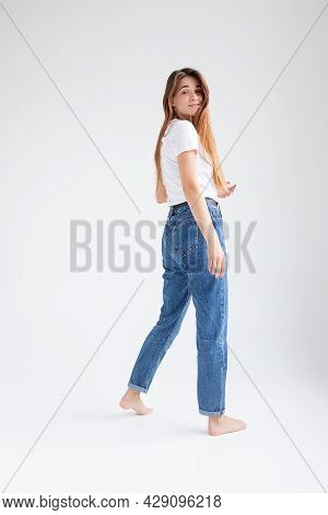 Young Attractive Caucasian Woman With Long Hair In T-shirt And Blue Jeans Isolated On White Studio B